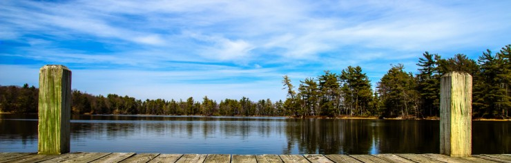 Summer Day At The Lake. Wooden dock overlooking a gorgeous lake in the wilderness. Ludington State Park. Ludington, Michigan.